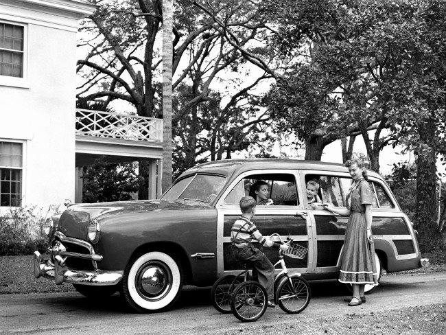 1949 Ford woodie wagon in front of home with family