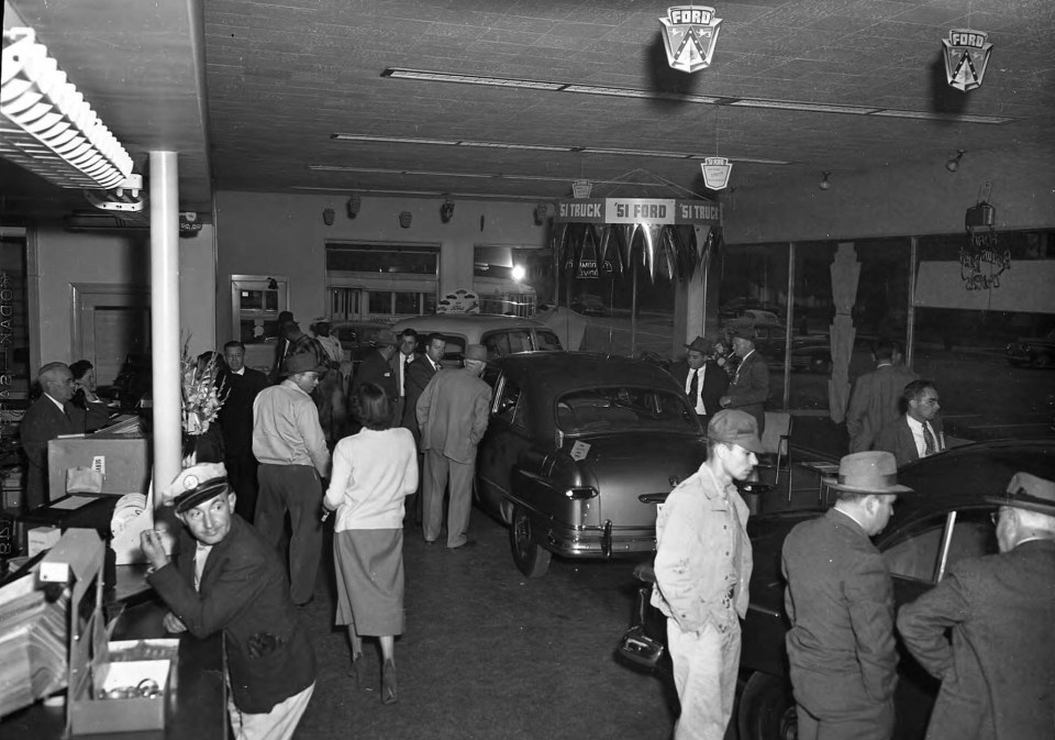 Crowd and counter in Wilson Motor Co. Showroom __ John Hensel Photograph Collection