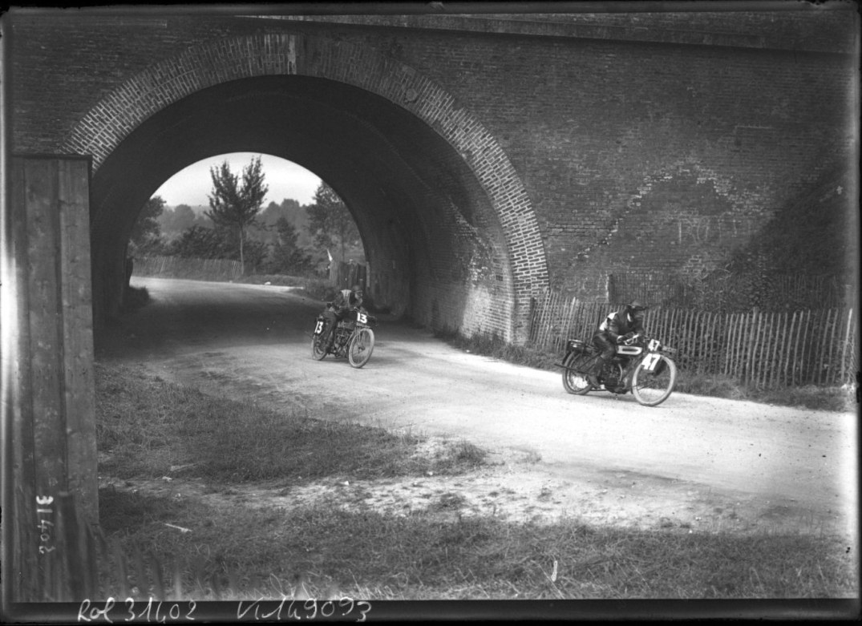 13-7-13, Amiens, [grand prix des motocyclettes], G. Fenton sur Clément, Cleyton sur Triumph [en course sous un petit tunnel] _ [photographie de presse] _ [Agence Rol]