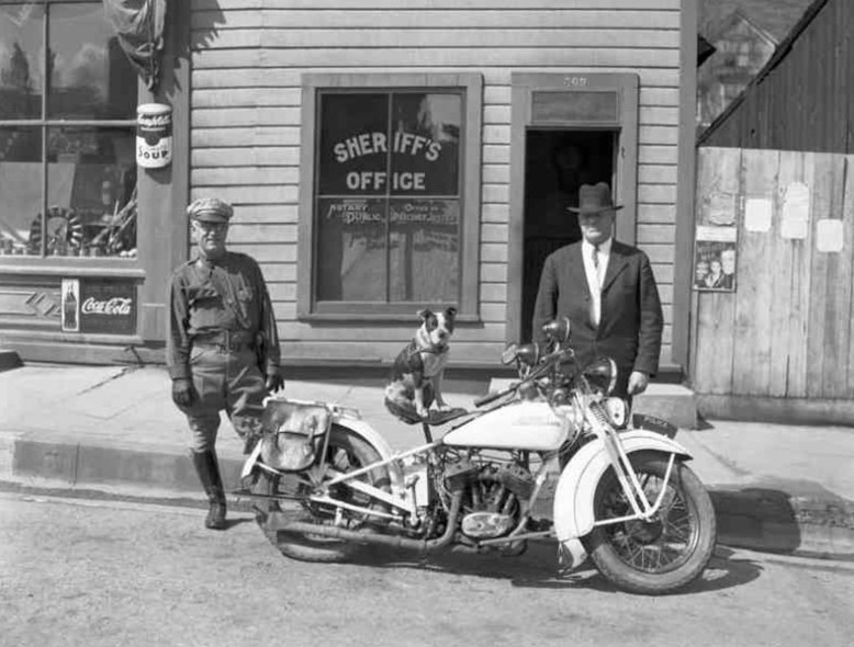 Officers with dog sitting on motorcycle __ Park City Historical Society & Museum