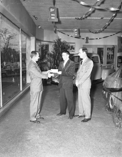 Wilson Motors, men exchanging check in showroom __ John Hensel Photograph Collection