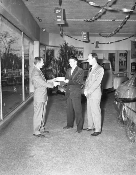 Wilson Motors, men exchanging check in showroom __ John Hensel Photograph Collection
